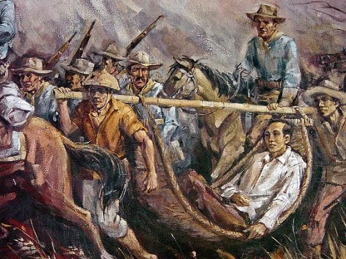 Apolinario Mabini resting in a hammock as men took turns at carrying him.