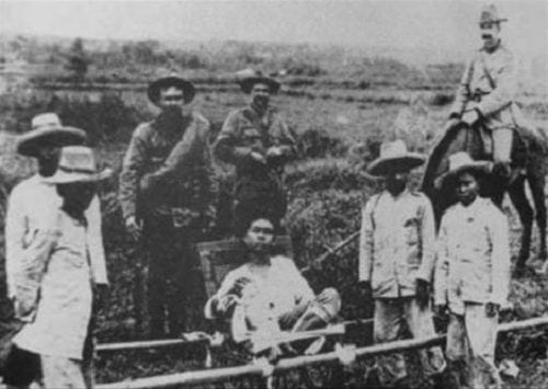 A man on a hammock (presumably Apolinario Mabini) guarded by Americans