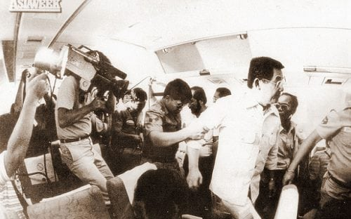 Ninoy being escorted by military people from China Airlines